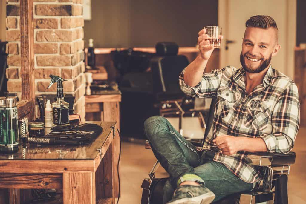 Homem brindando com um copo de whisky
