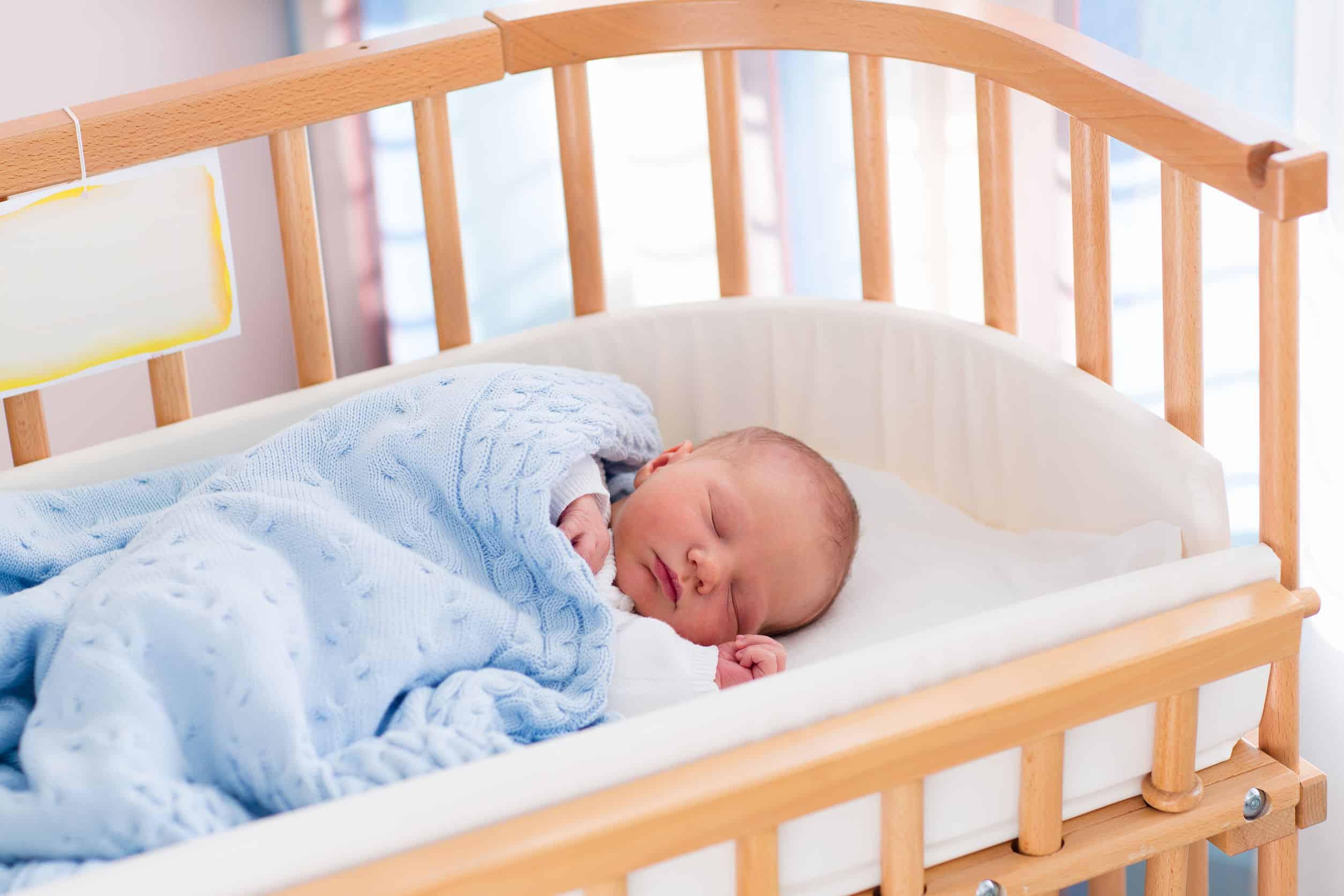 Bebê dorme tranquilamente em uma caminha com grades de madeira
