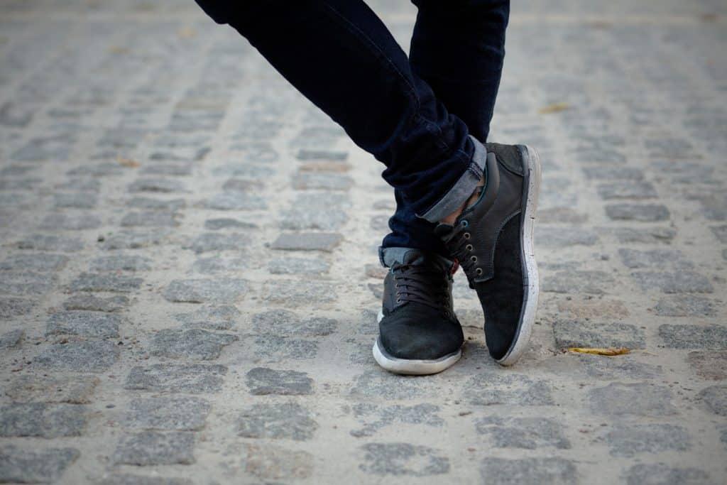 Imagem mostra os pés de uma pessoa calçando um tênis esportivo na calçada.