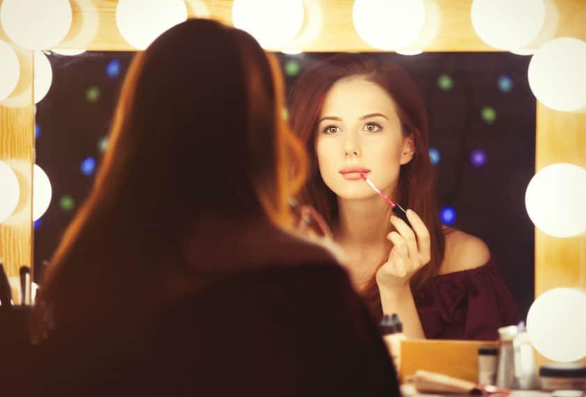 Mulher em frente ao espelho se maquiando.