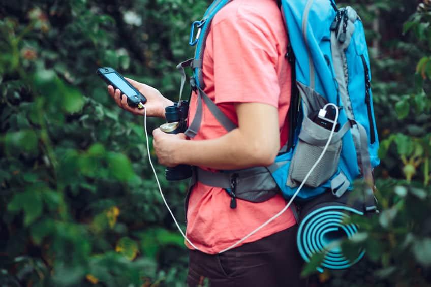 Imagem de homem com mochila carregando celular.