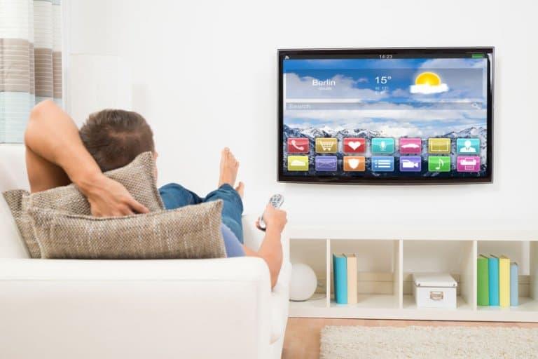 Homem em sofá assistindo TV.