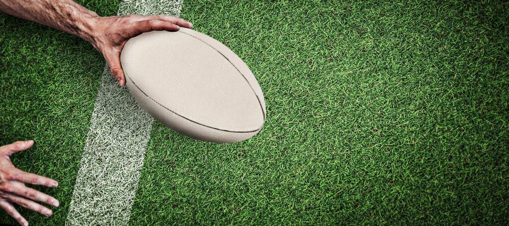 Bola de rugby branca em gramado.