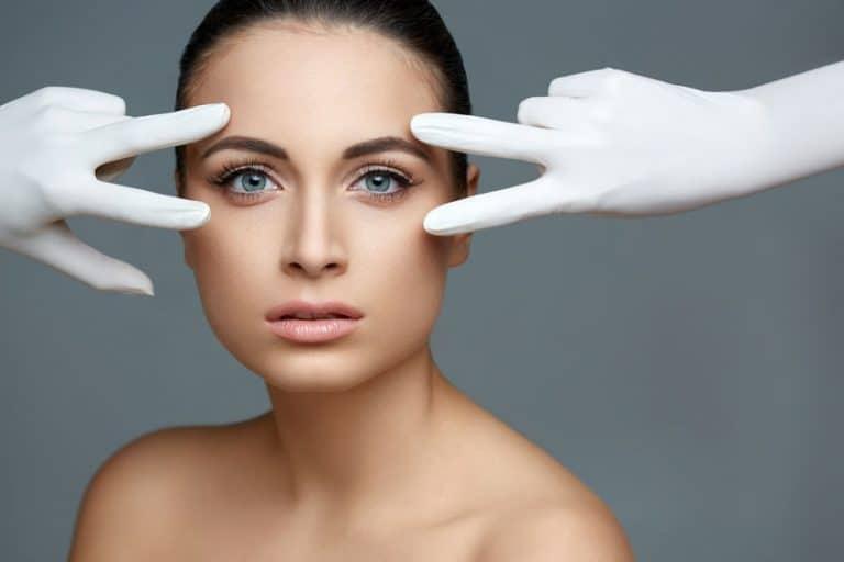 Mulher com expressão séria com duas mãos brancas próximo aos olhos dela.