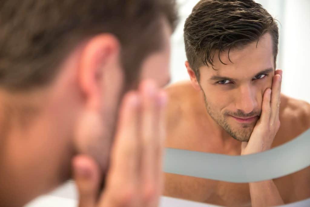 Imagem de homem olhando no espelho.