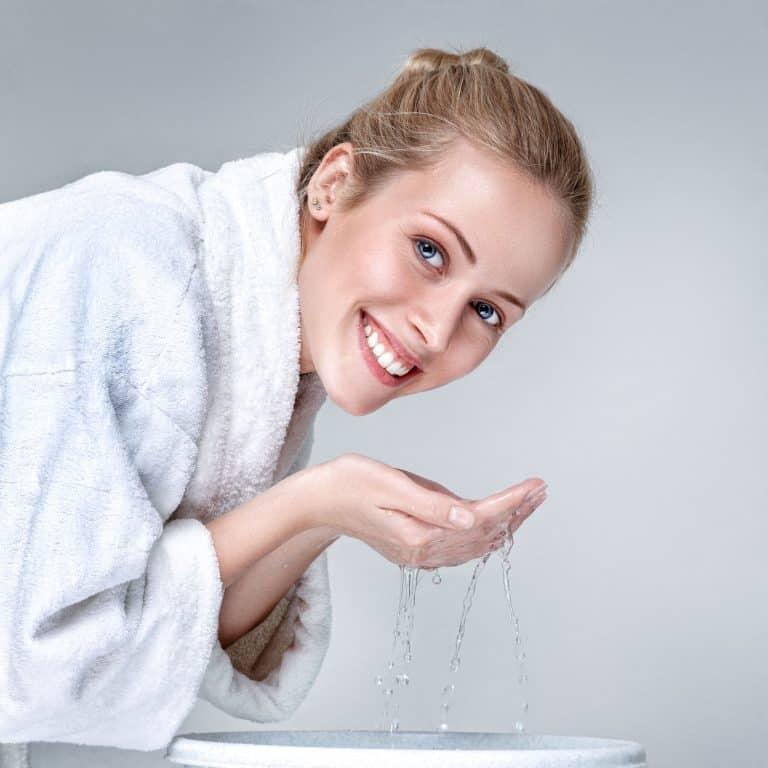 Mulher sorrindo lavando o rosto.
