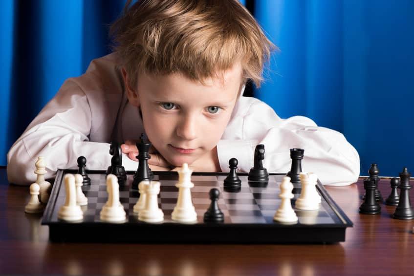 Menino olhando para tabuleiro de xadrez.