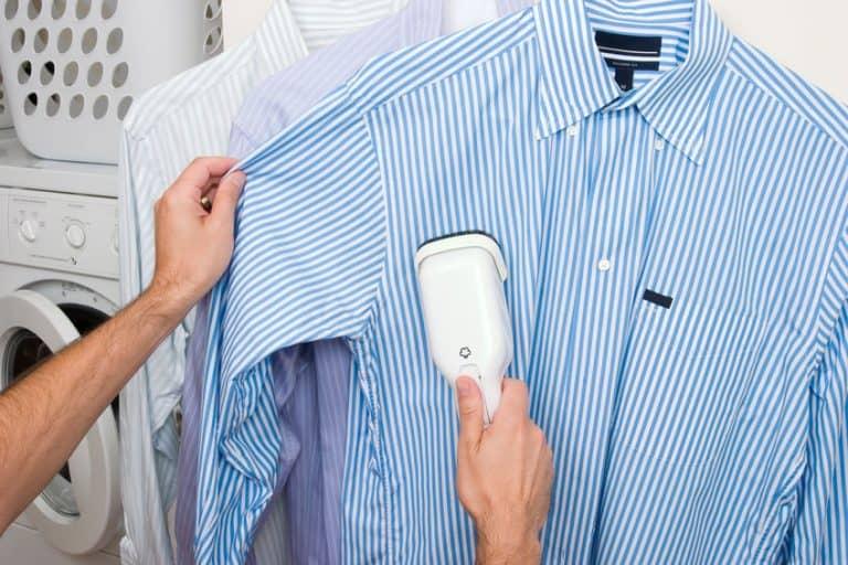 Imagem de pessoa passando vaporizador em camisa social de listras azuis.