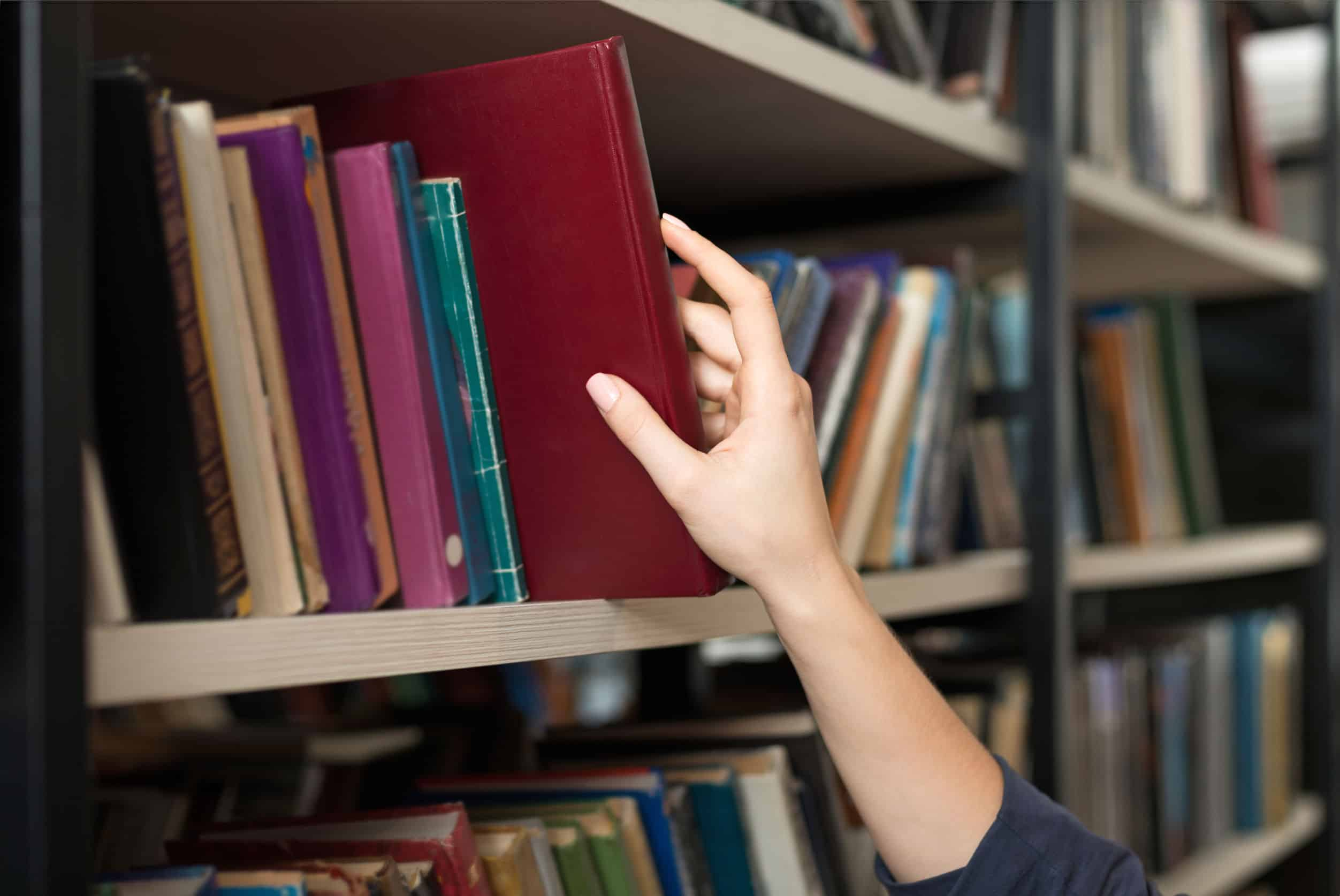 Imagem de mão pegando livro em estante de biblioteca.