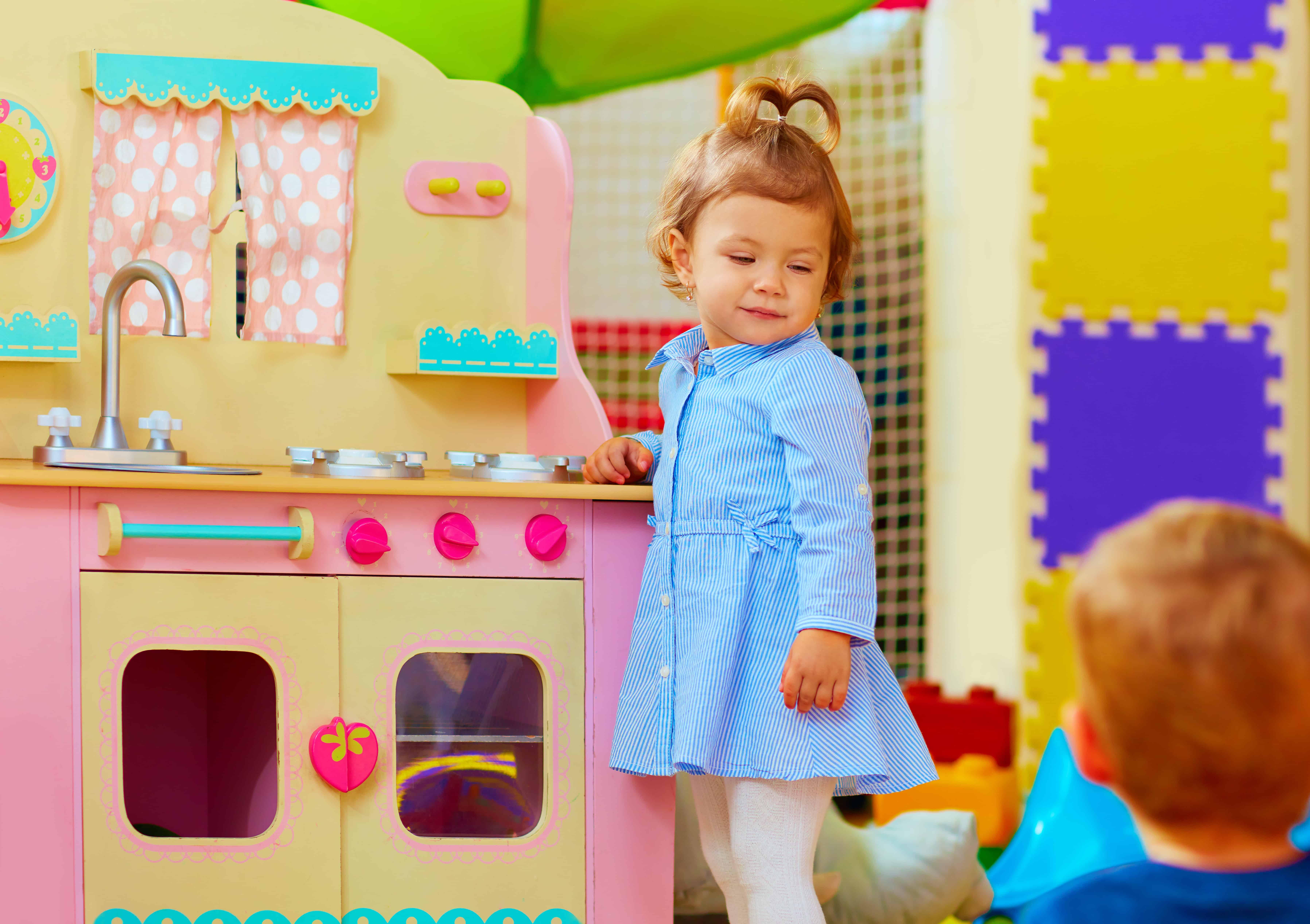 Menina e cozinha de brinquedo.