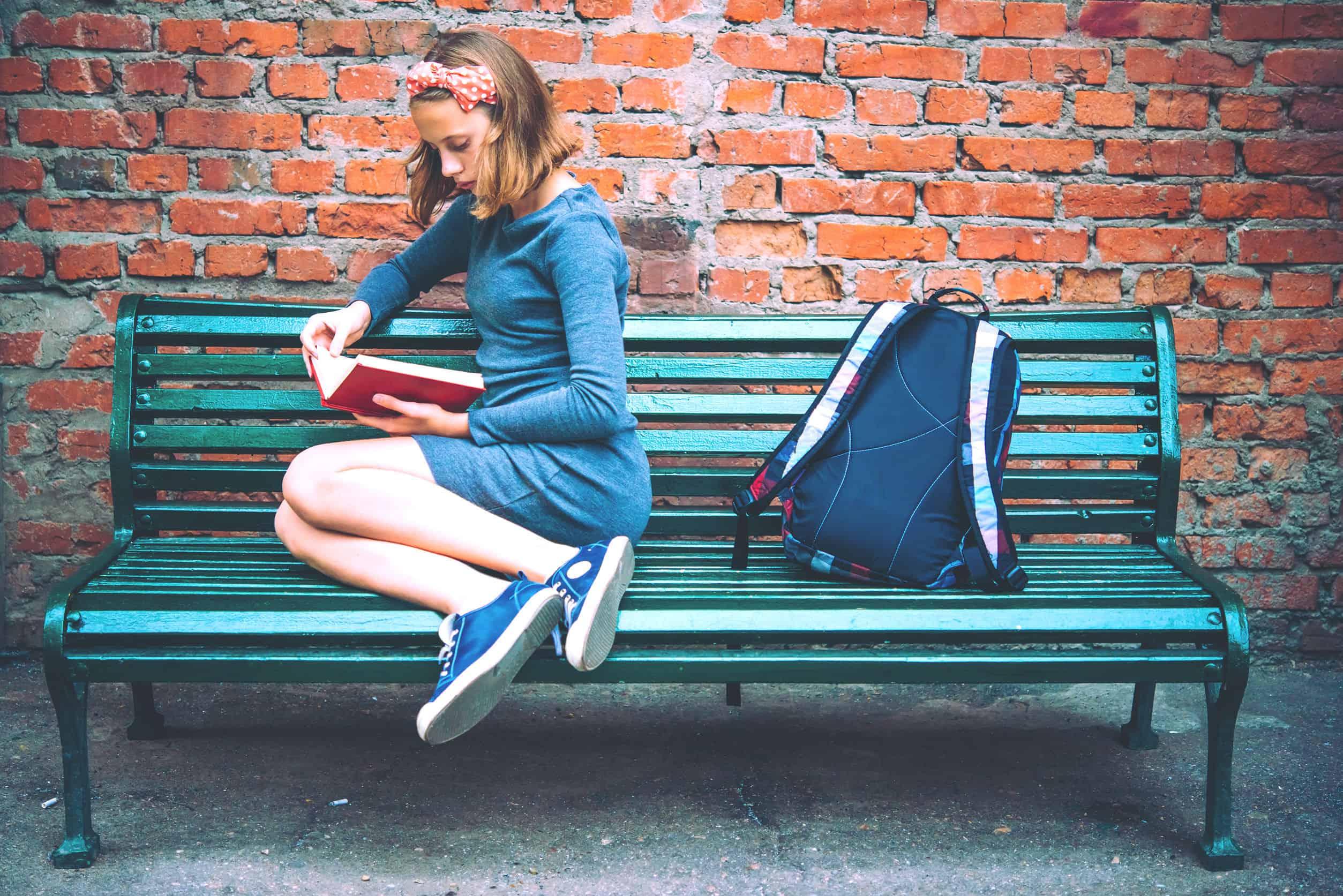 Imagem de menina sentada em banco azul com mochila do lado.