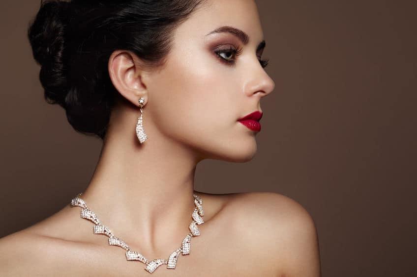 Mulher de perfil com joias e batom vermelho