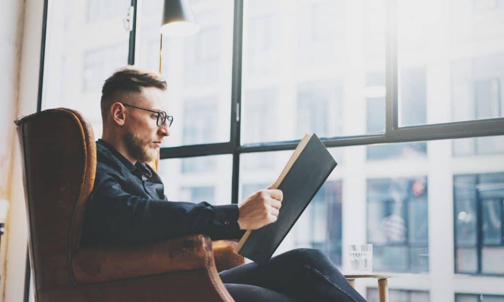 Imagem de homem lendo livro em janela.