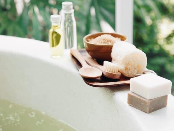Imagem de sais de banho, sabonete e óleo sobre banheira.