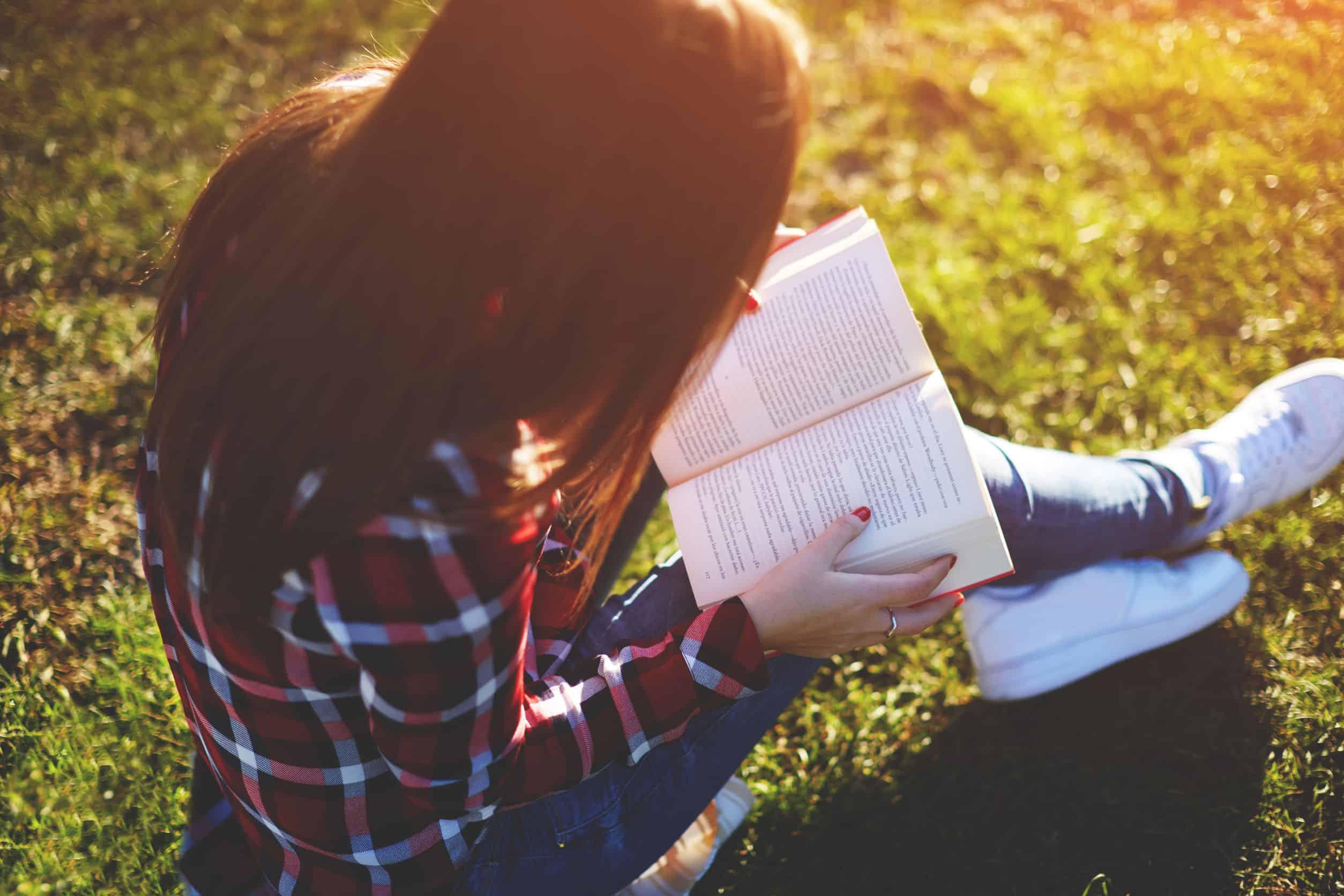 Imagem de menina lendo livro.