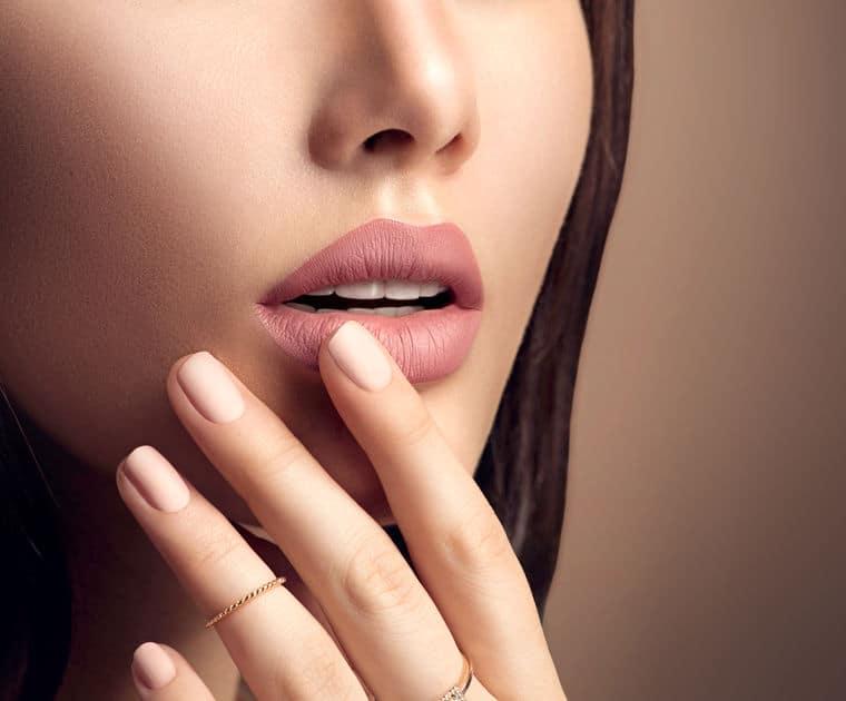 Rosto de mulher usando batom matte e com mão próxima à boca
