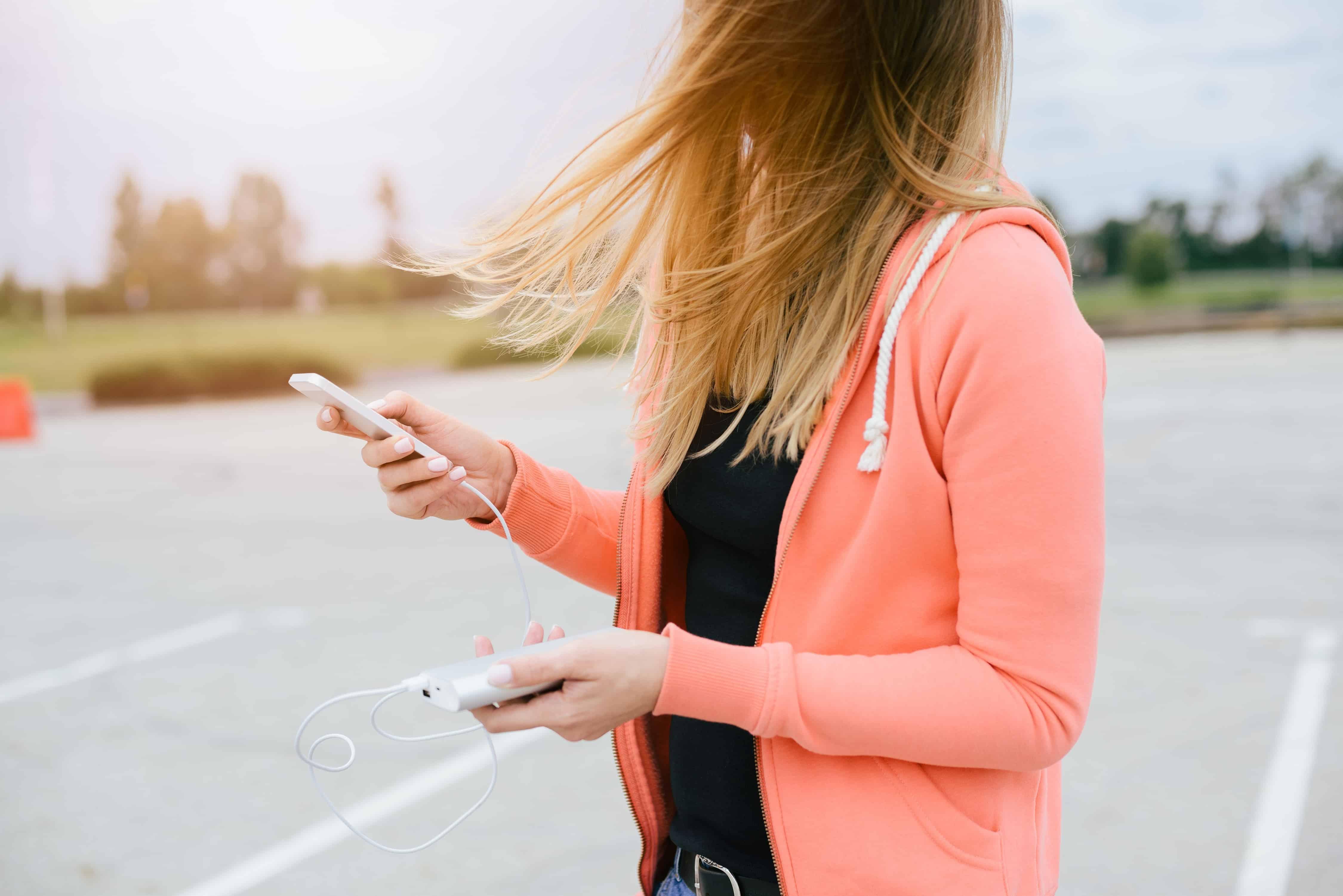 Mulher segurando um carregador portátil na rua