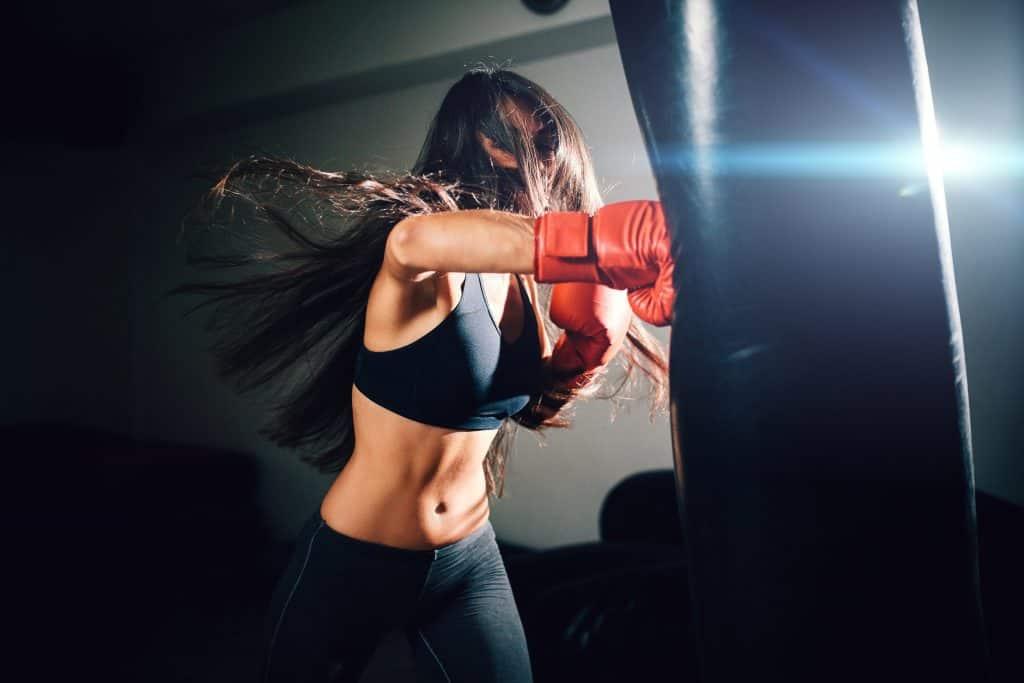 garota com luvas vermelhas batendo em um saco de pancada preto