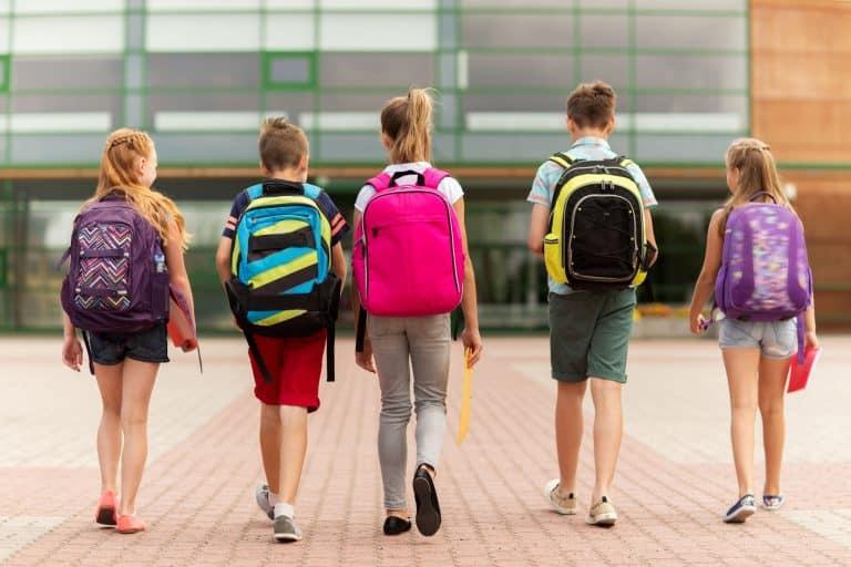 Crianças caminhando com mochila nas costas.