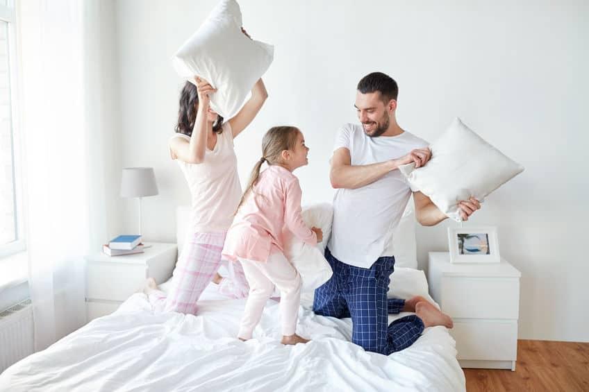 Imagem de família em cima de cama brincando com travesseiros.