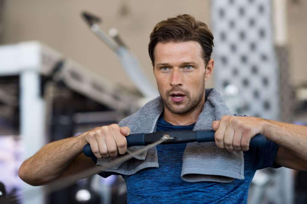 Homem se exercitando com um simulador de remo
