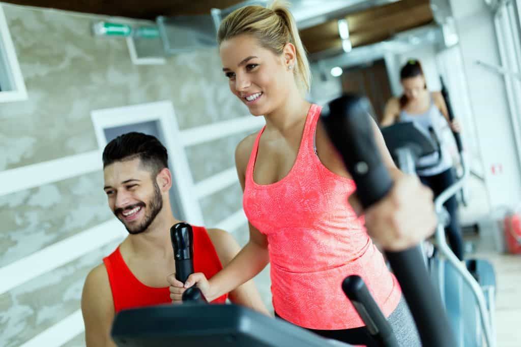 mulher fazendo exercício no elíptico com treinador ao lado