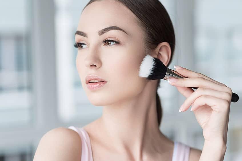 Mulher passando maquiagem no rosto com pincel.