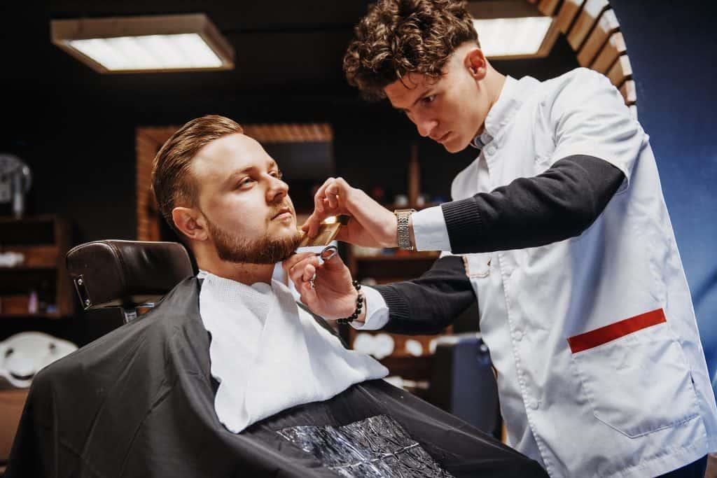 Imagem de homem sentado em cadeira de barbearia com barbeiro fazendo sua barba.