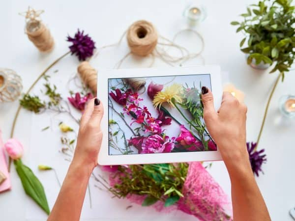 Top view closeup of female hands holding digital tablet and taking photo of floral decor composition for social media