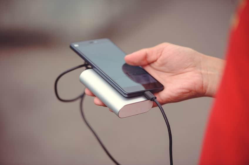 Carregando celular com carregador portátil.