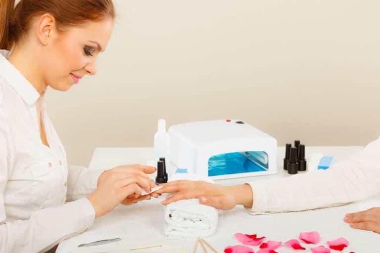 Mulher fazendo as unhas com manicure.