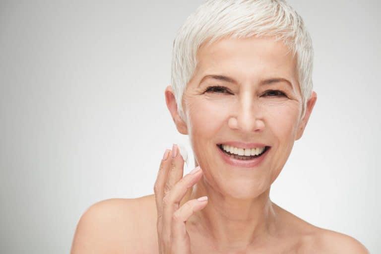 Imagem de mulher mais velha passando creme antirrugas.