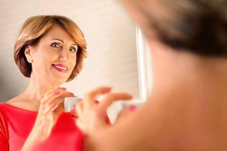 Mulher de meia idade na frente do espelho segurando pote de creme.