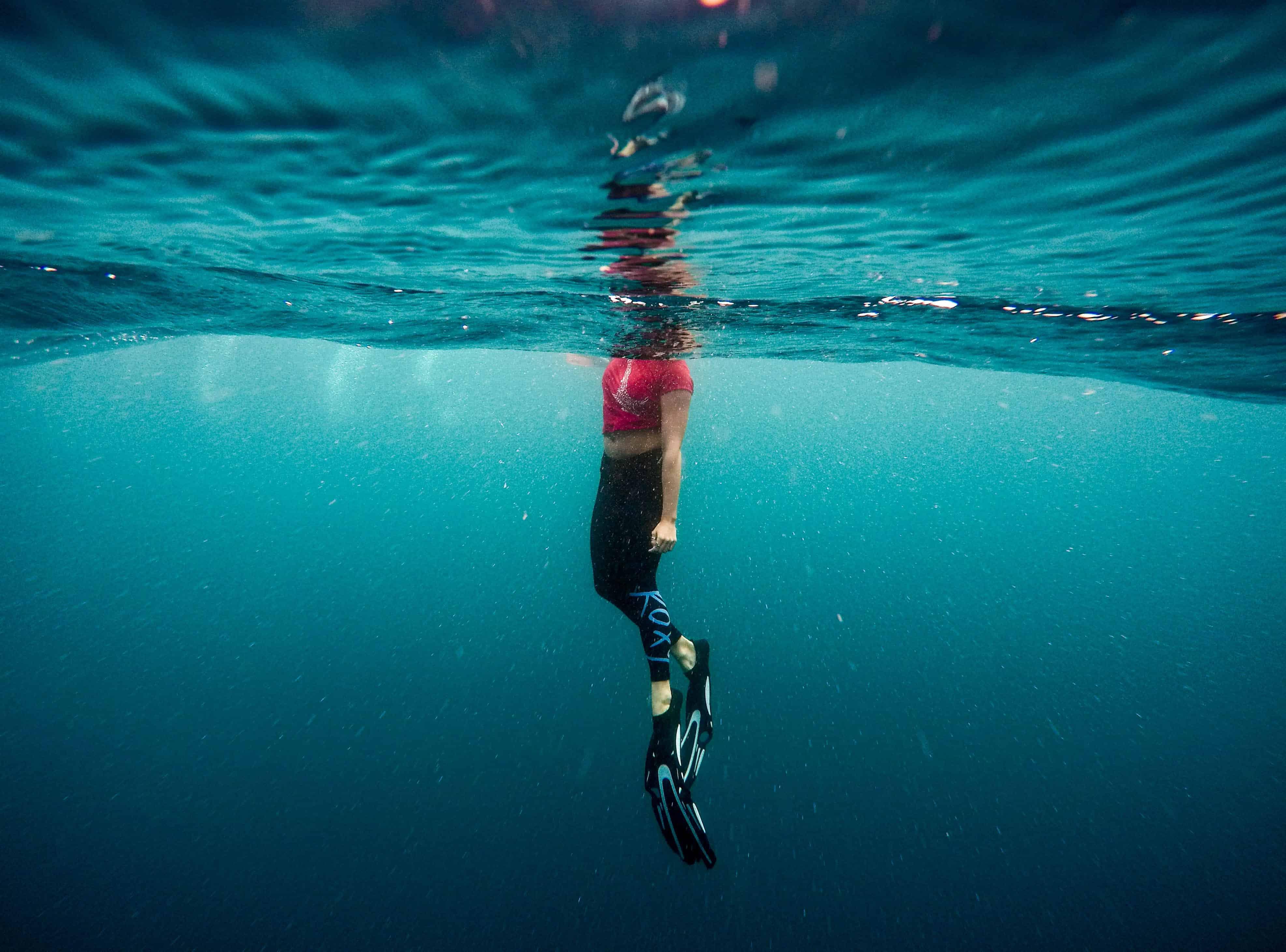 Mulher nadando com pés de pato.