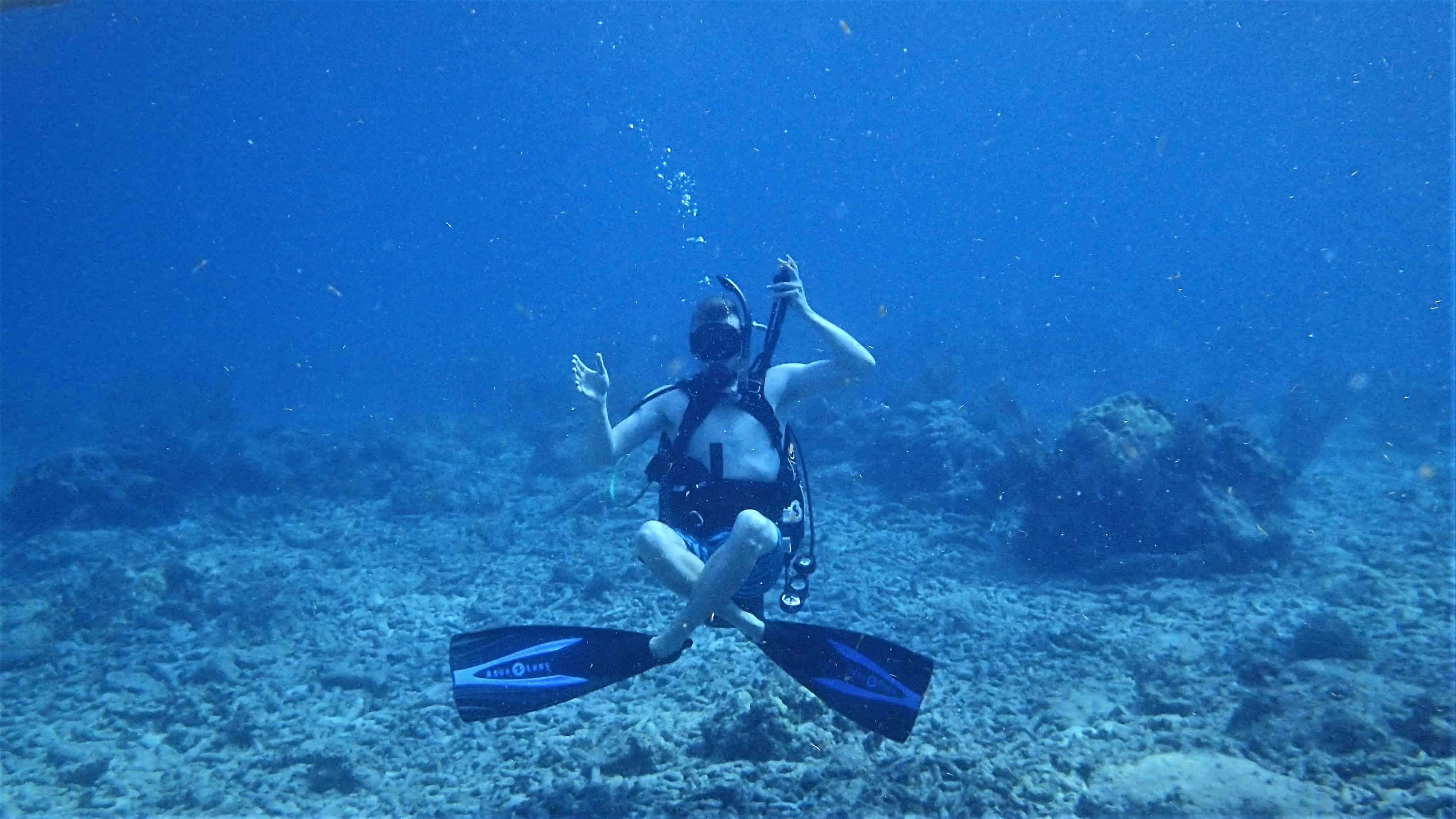 Imagem de nadador no fundo do mar com pé de pato.