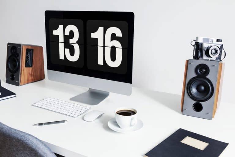 Imagem de computador em mesa com caixas de som ao lado.