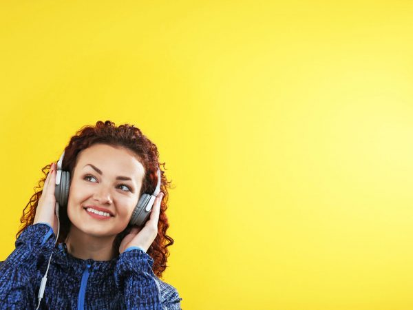 Attractive woman listening to music with headphones on yellow background