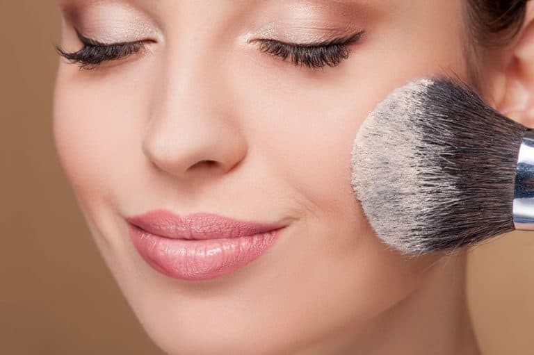Imagem mostra uma mulher passando maquiagem.