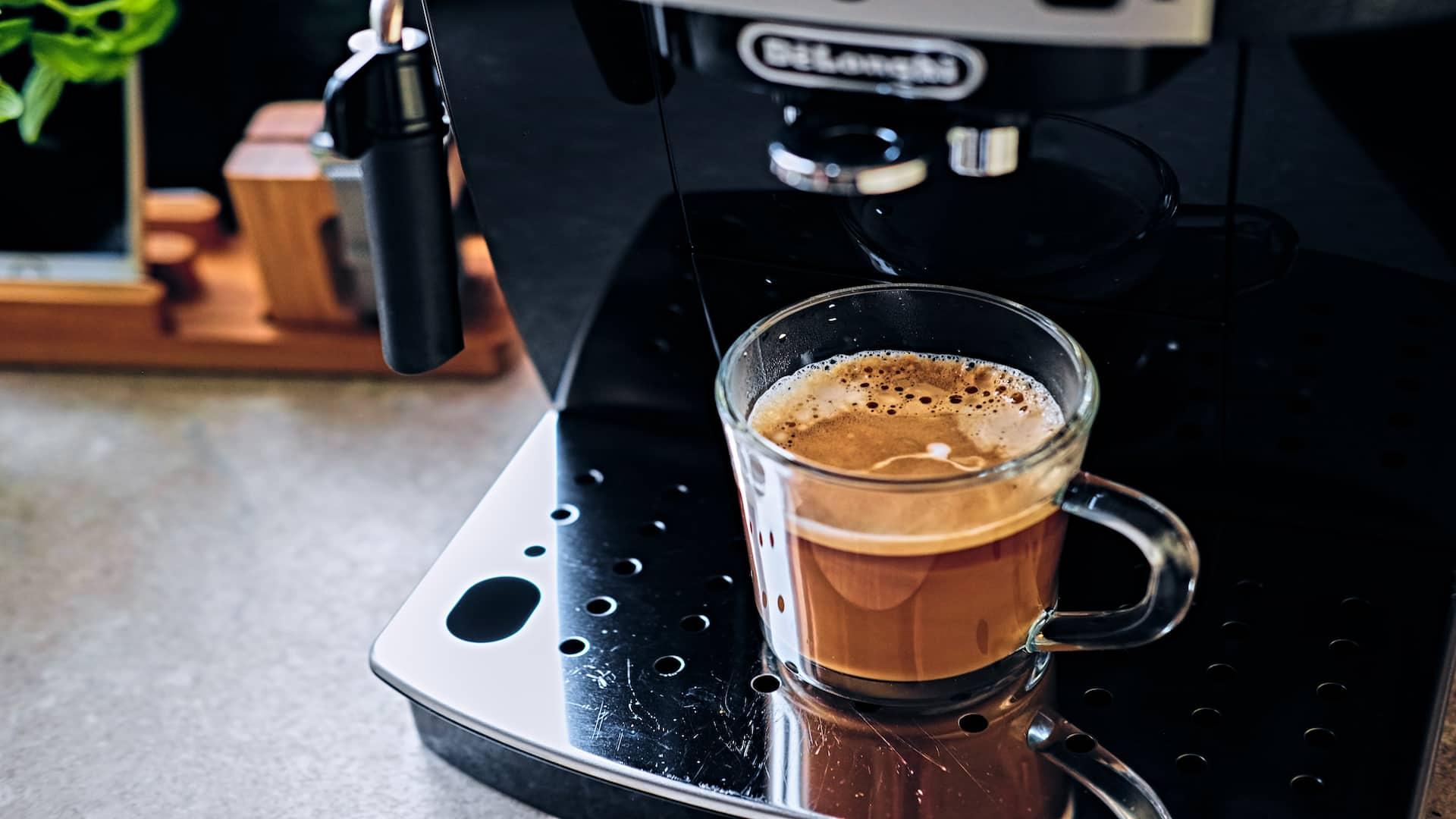 Imagem mostra máquina de café com xícara de café cheia.
