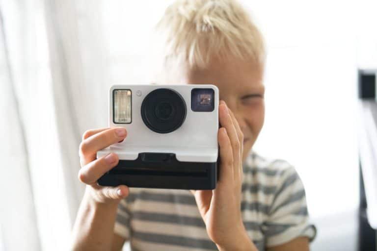 Imagem de menino loiro com camiseta listrada segurando câmera instantânea.