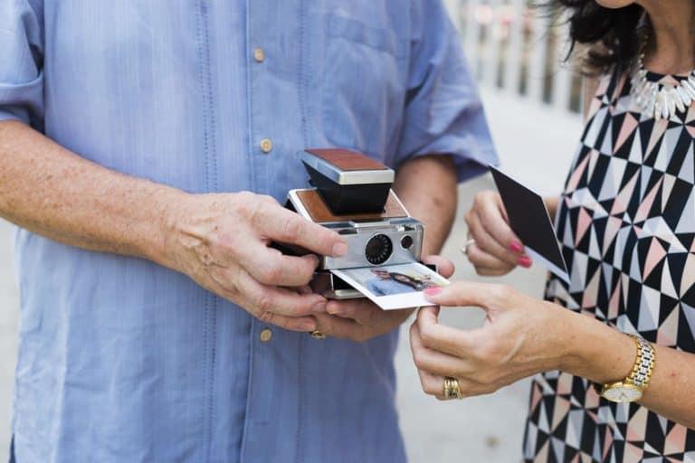 Imagem de casal segurando câmera instantânea com foto saindo dela.