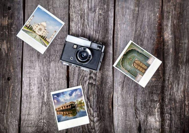 Imagem de câmera instantânea sobre mesa e fotos ao lado.
