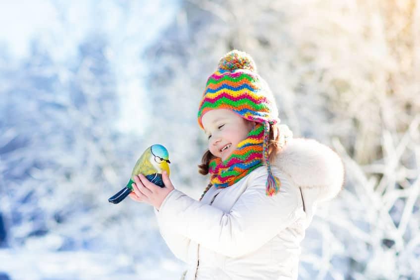 Imagem de menina segurando pássaro.