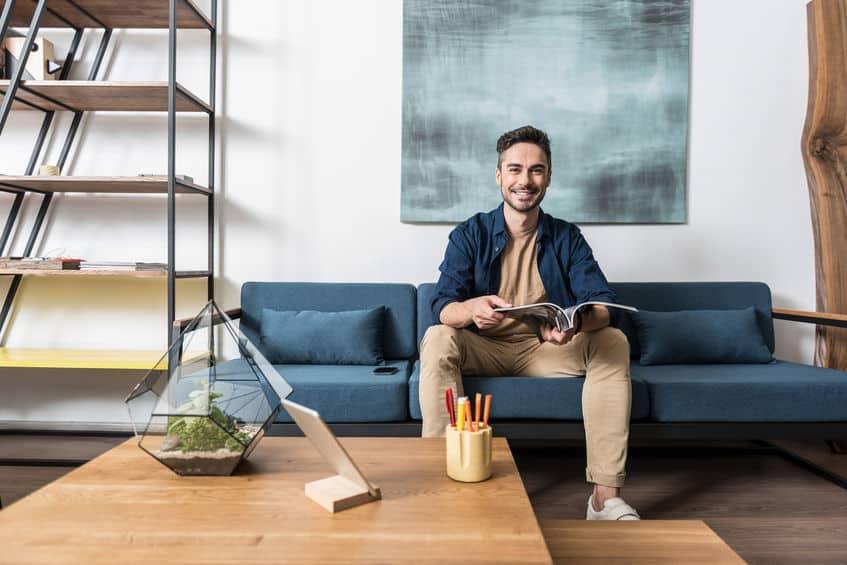 Imagem de homem sentado em sofá com HQ na mão.