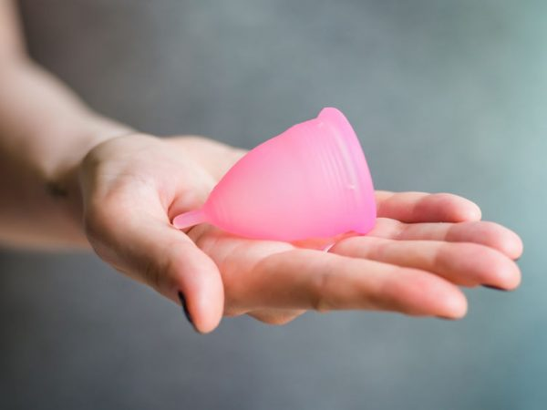 Young woman hand holding menstrual cup