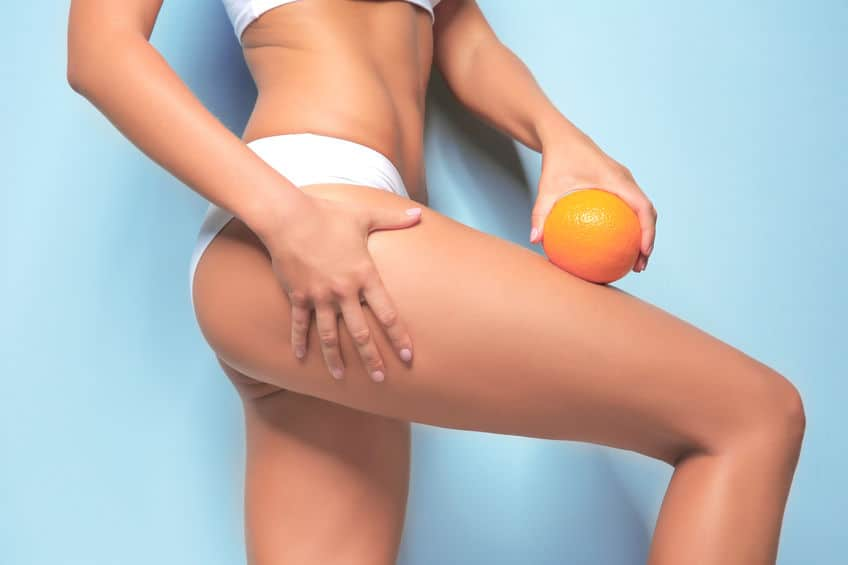 Mulher com laranja na perna.