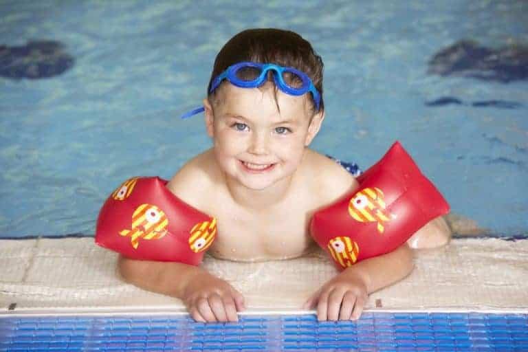 Menino na beira de piscina com bóia de braço e óculos de natação na cabeça.