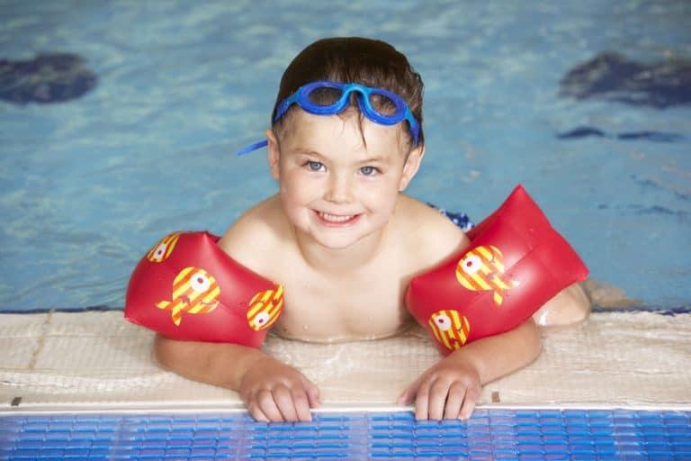 Imagem de criança na borda da piscina com óculos de natação e boia de braço.