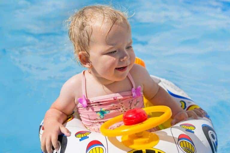 Imagem de menina em bóia dentro de piscina.