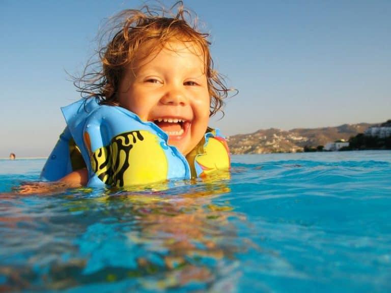 Criança com boia em piscina.